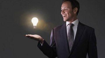 Portrait of mid adult man with illuminated light bulb